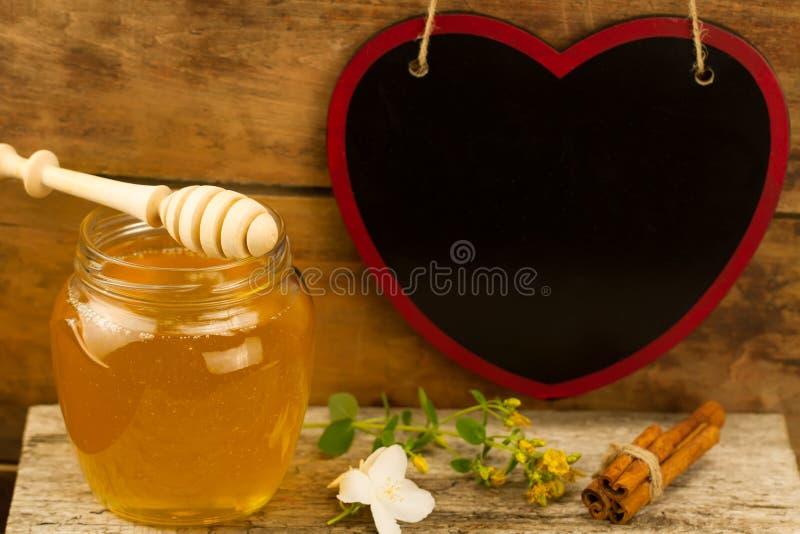 Kruik verse honing met drizzler, kaneel, bloemen op houten achtergrond royalty-vrije stock afbeeldingen