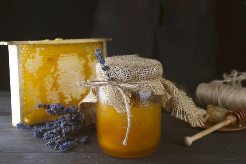 Kruik vloeibare honing met honingraat royalty-vrije stock afbeeldingen