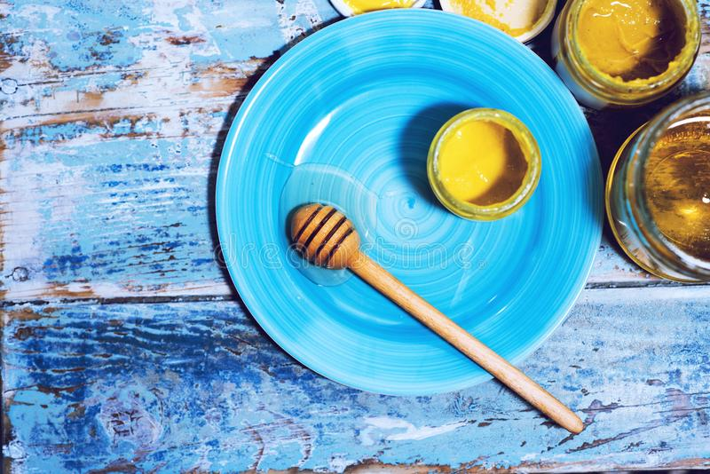 Kruiken met honing en citroen en een honingsopruier op een blauwe plaat royalty-vrije stock fotografie