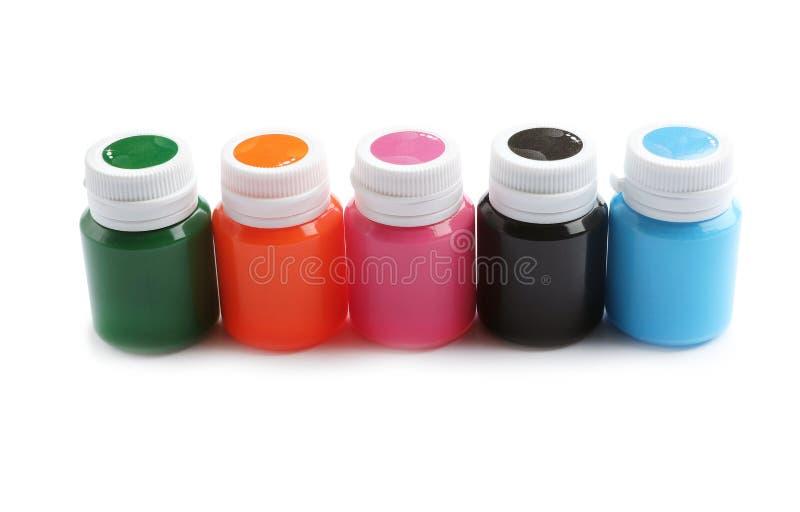 Kruiken met kleurrijke verven op witte achtergrond Artistieke apparatuur stock foto