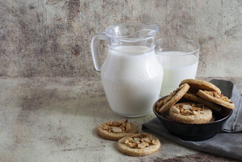 Kruimelige koekjes met pinda's op een plaat die zich op de lijst bevindt Een waterkruik melk en een glas melk op een mooie grijze royalty-vrije stock afbeelding