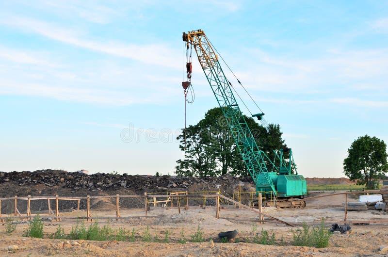 Kruippakjekraan op de bouwwerf voor het laden en het leegmaken en bouwwerkzaamheden voor het leggen van rioolpijpen stock foto's