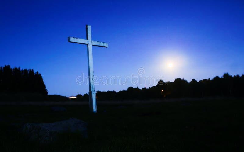 Kruis bij nacht tegen hemel, maan op achtergrond stock foto