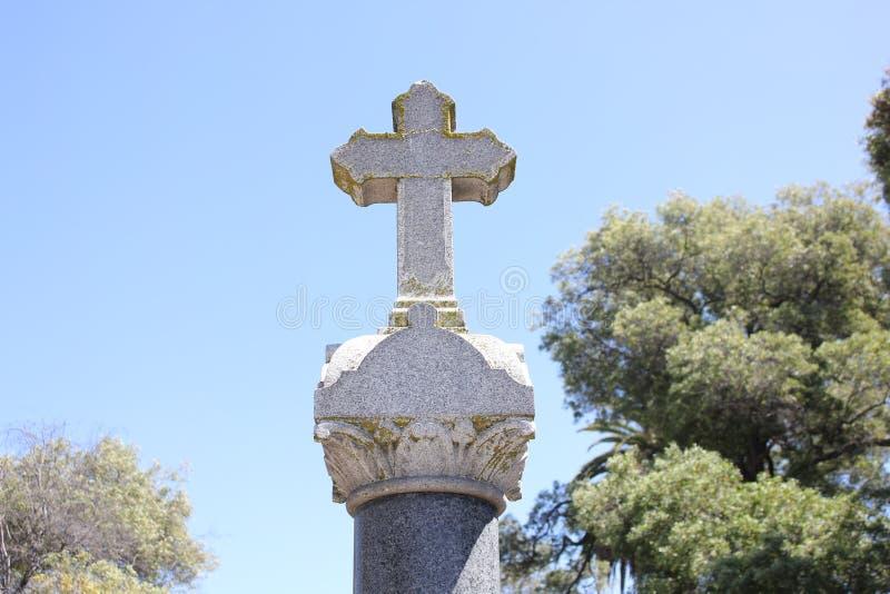 Kruis bovenop grafsteen stock fotografie