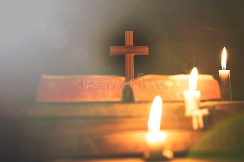 Kruis met bijbel en kaars op een oude eiken houten lijst Mooie gouden achtergrond royalty-vrije stock afbeeldingen