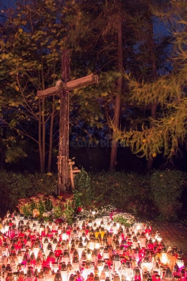 Kruis met kaarsen op Poolse begraafplaats tijdens Al Zielen` Dag bij nacht stock afbeeldingen