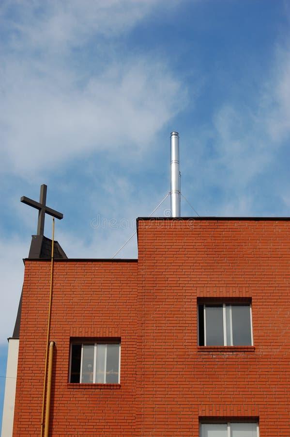 Kruis op de bovenkant van de kerk en de blauwe hemel stock foto