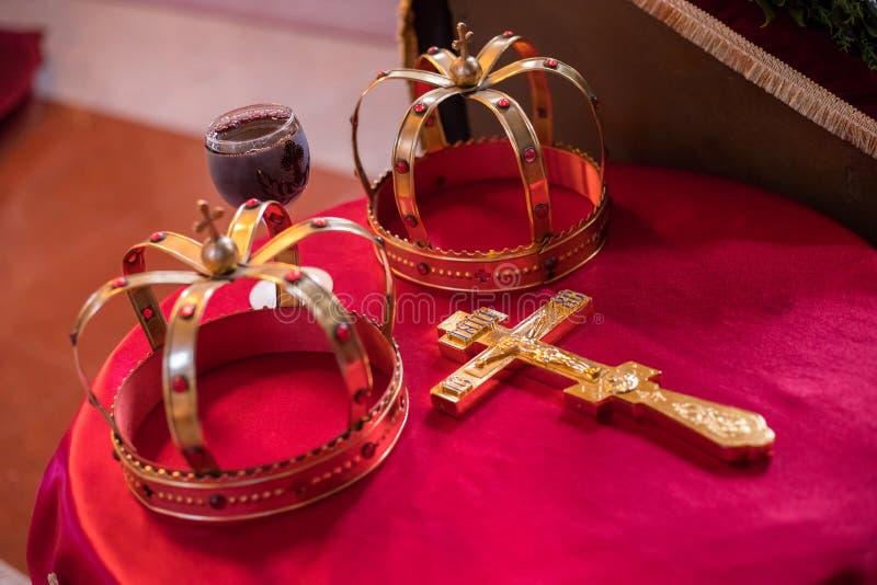 Kruis, twee kronen en glas van wijnstok op rode die lijst op huwelijk wordt voorbereid De orthodoxe toebehoren van het kerkhuweli stock foto's