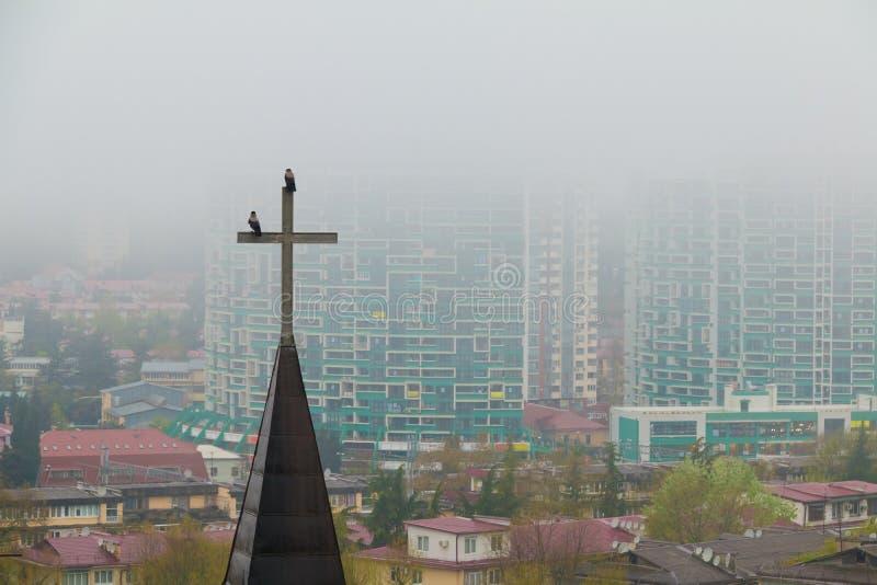 Kruis van kerk op achtergrond van Sotchi in mist, Rusland stock afbeeldingen