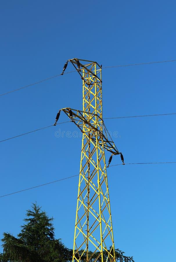 Kruisen de hoogspannings elektrische lijnen de heuvelige mestnost Elektrische post in de zomer onder de open hemel Getelegrafeerd stock foto's