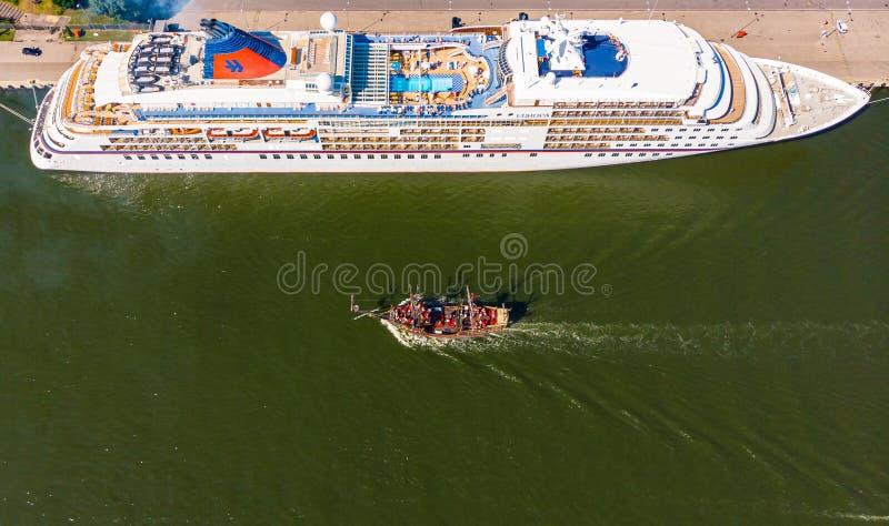 Kruiserschip en kleine toeristenboot in haven Gdansk royalty-vrije stock afbeeldingen