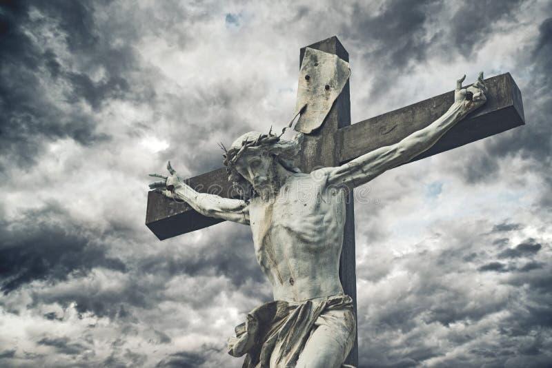 kruisiging Christelijk kruis met Jesus Christ-standbeeld over onweer stock fotografie
