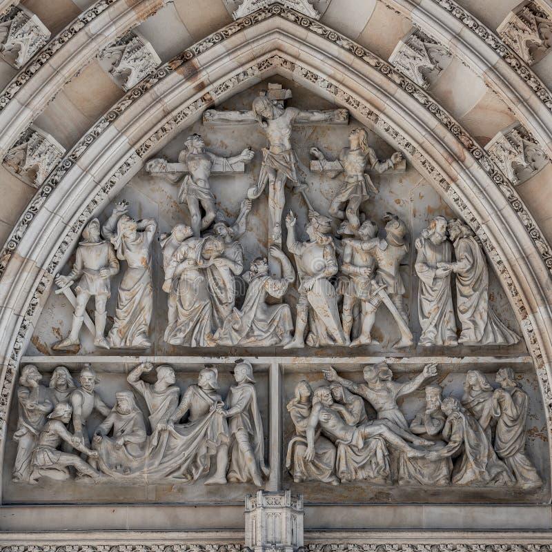Kruisiging van de scène van Christus bij belangrijk ingangsportaal van Heilige Vitus Cathedral in Praag, Tsjechische Republiek, d royalty-vrije stock fotografie