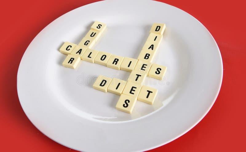 Kruiswoordraadselspel op schotel op lijst rode mat met woordensuiker, calorieën, diabetes en dieet die in de gezondheidsrisico va royalty-vrije stock foto's