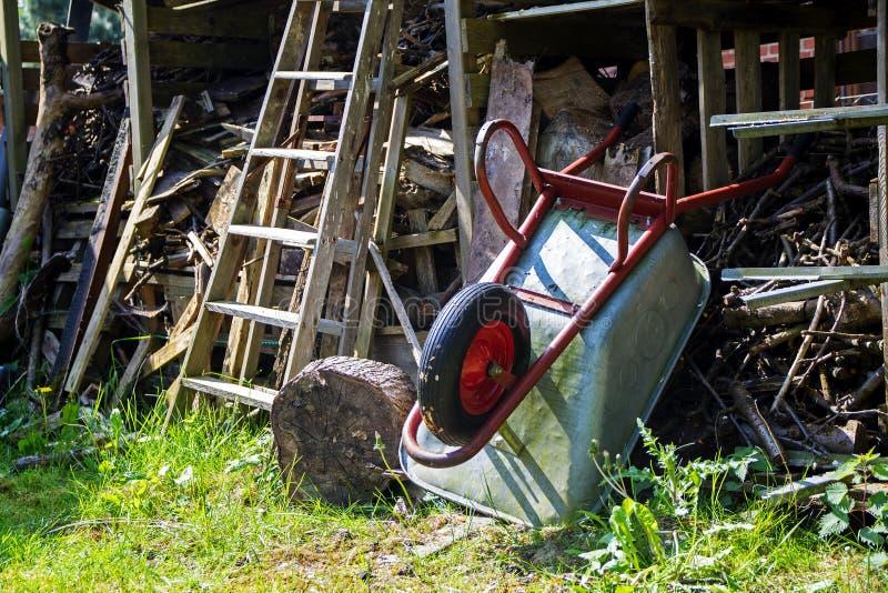 Kruiwagen die boven op een loods met slordig gestapeld hout leunen royalty-vrije stock fotografie