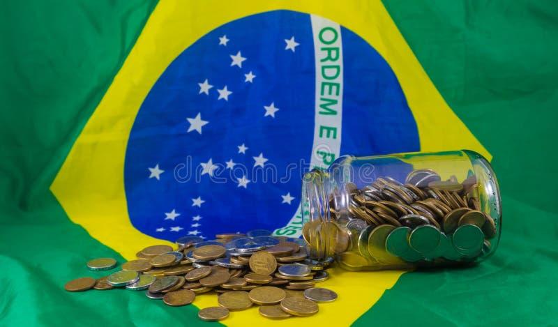 Kruka av brasilianska mynt, på bakgrundsflaggan av Brasilien Finansiell verklighet royaltyfri foto