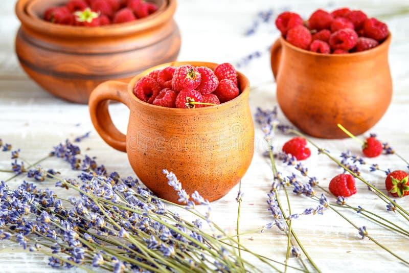 Krukmakeri med jordgubbar och lavendel på trätabellen royaltyfria bilder