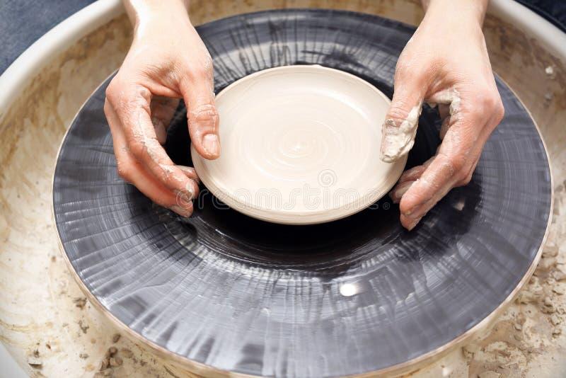 Krukmakeriseminarium som arbetar på ett hjul för keramiker` s arkivbilder