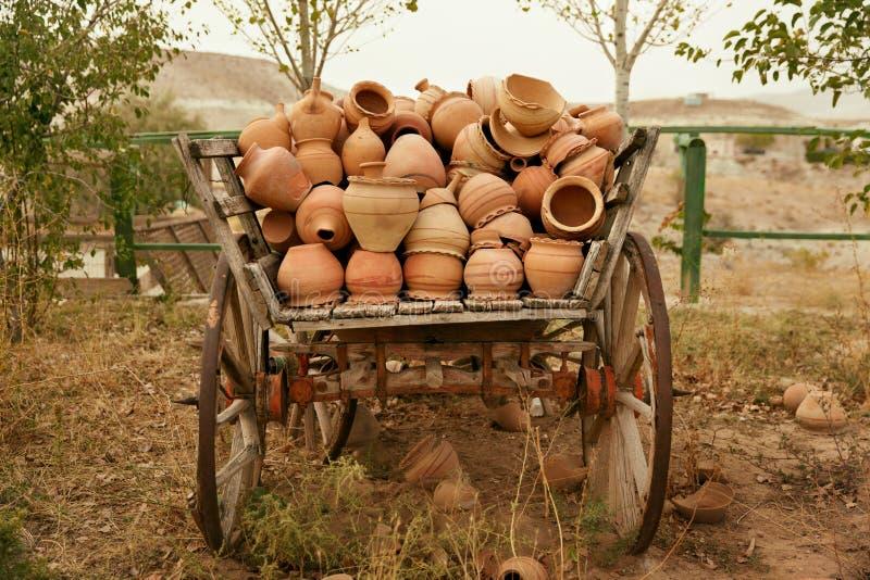 Krukmakeritillbringare i träCartload, handgjorda keramiska Clay Crockery arkivfoton