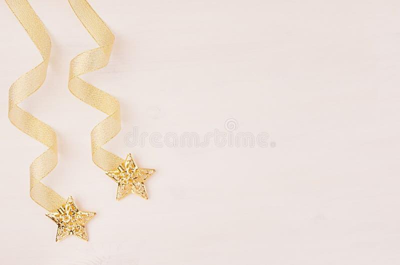 Krulla band- och guldstjärnor som faller på mjuk vit träbakgrund royaltyfri fotografi