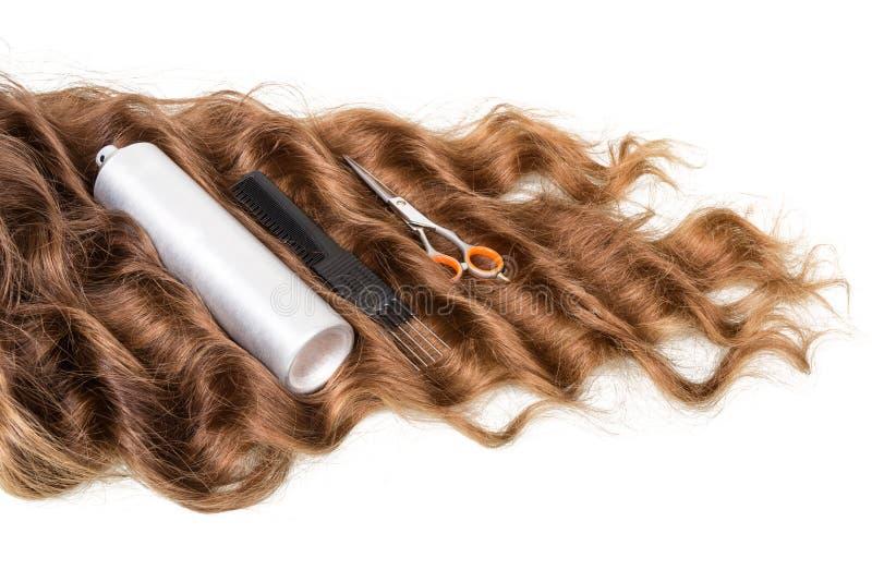Krullad hårtråd, hjälpmedeluppsättning och sprej på vit royaltyfri bild
