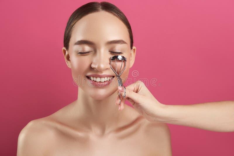 Krullande ögonfrans för kosmetolog av den glade unga damen royaltyfri fotografi