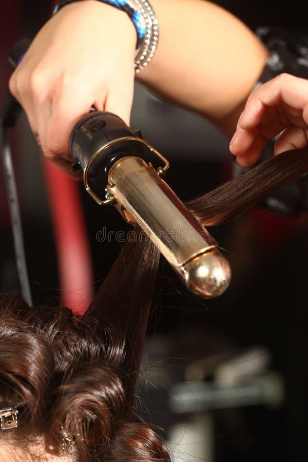 Krullande hår för funktionsduglig Hairstylist i en salong royaltyfria foton