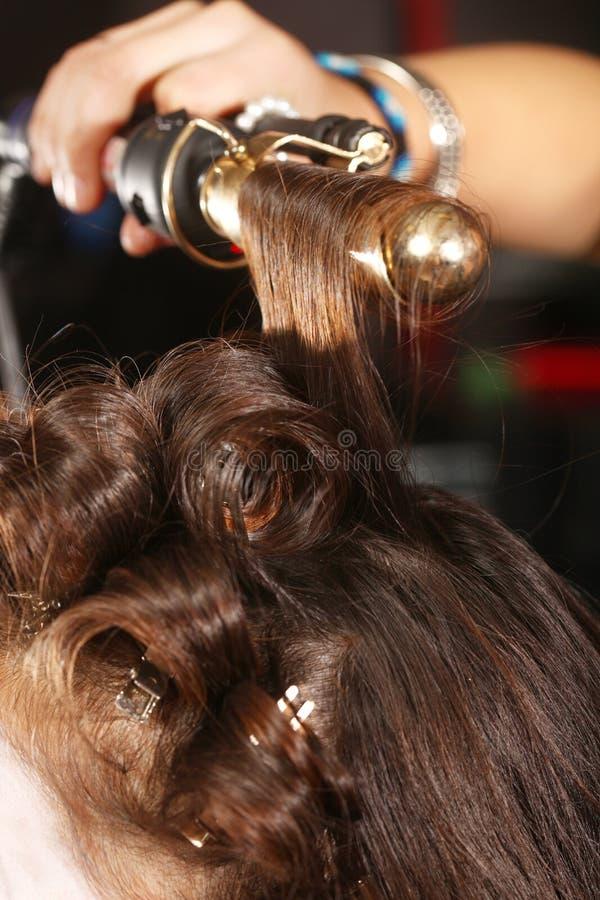 Krullande hår för funktionsduglig Hairstylist i en salong fotografering för bildbyråer