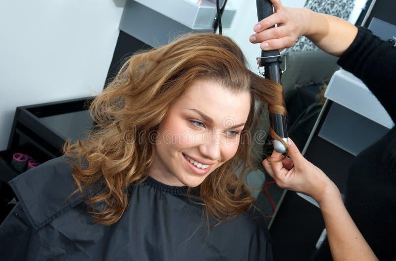 Krullande hår för kvinna i hairsalon royaltyfri fotografi