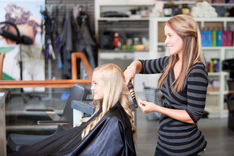 Krullande kvinnas för stylist hår arkivfoto
