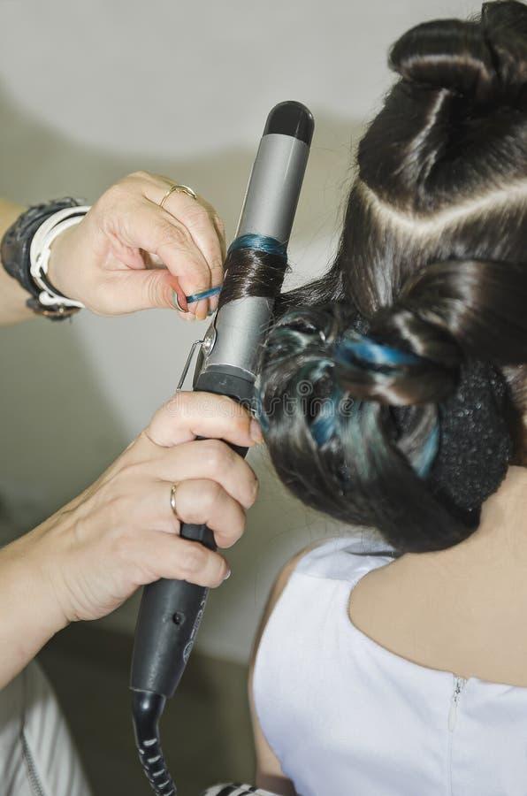 Krullande kvinnas hår som ger en ny frisyr på closeupen för hårsalong royaltyfri bild