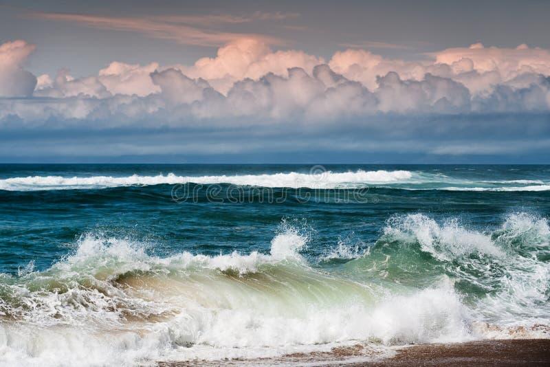 Krullen van Golven en Krullen van Wolken Grote golven die op de kust breken stock foto