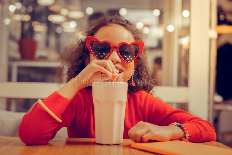 Krullend aantrekkelijk meisje die armbanden dragen die van haar milkshake genieten stock foto's