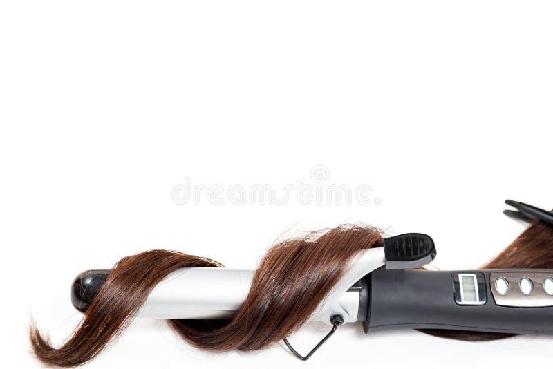 Krullend donker haar met een krullend ijzer dat op witte achtergrond wordt geïsoleerd stock foto