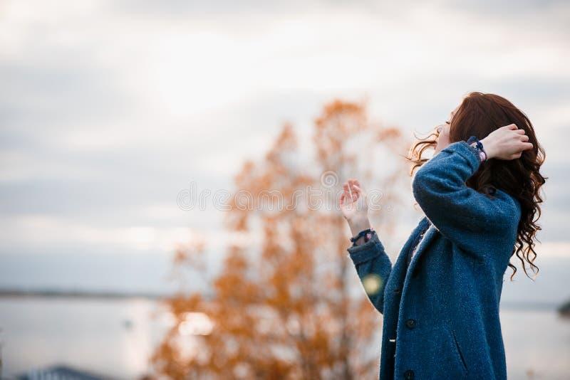 Krullend haar mooi jong Kaukasisch meisje die in openlucht blauwe laag dragen, die in de herfstpark stellen stock foto