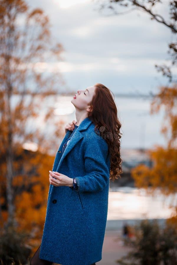 Krullend haar mooi jong Kaukasisch meisje die in openlucht blauwe laag dragen, die in de herfstpark stellen royalty-vrije stock fotografie