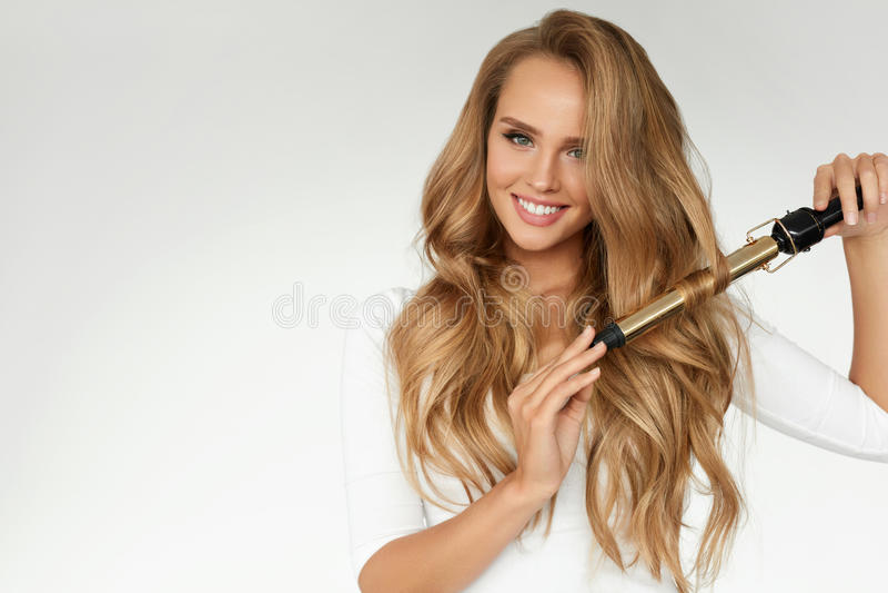 Krullend Haar Mooie Vrouw die Lang Golvend Haar met Ijzer krullen royalty-vrije stock foto