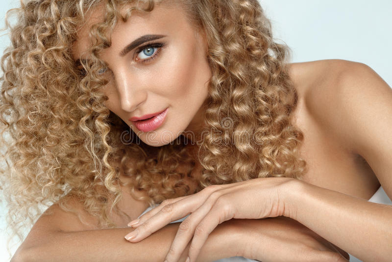 Krullend Haar Mooie Vrouw met Natuurlijke Schitterende Haarkrullen stock foto's