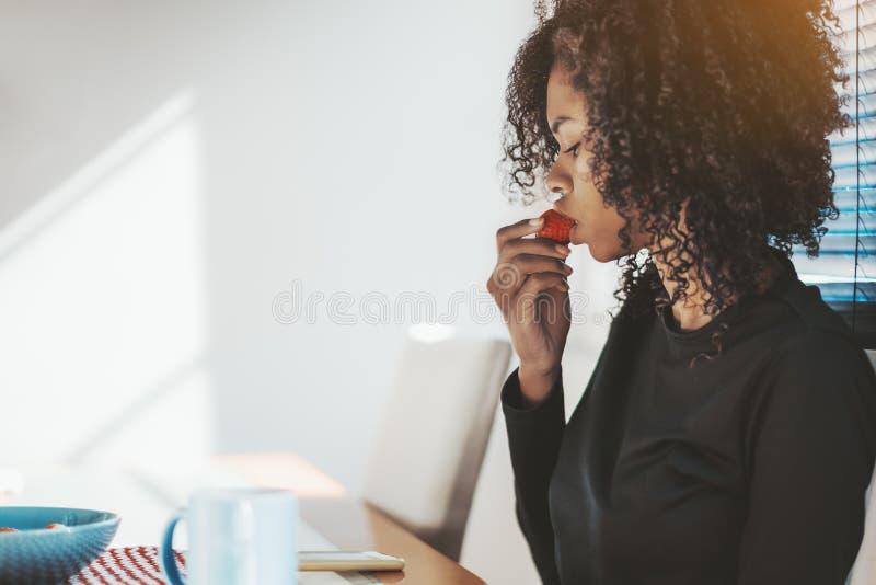 Krullend-haarmeisje die aardbei eten stock afbeeldingen