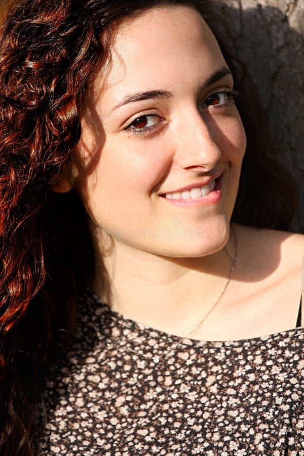 Krullend, mooi jong meisje met aardige glimlach stock foto's