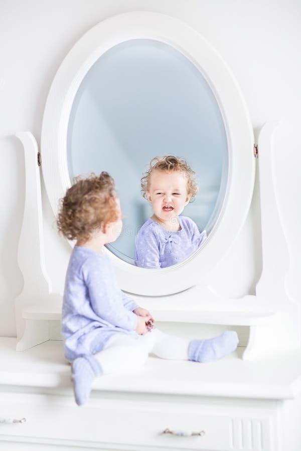 Krullend peutermeisje die grappige gezichten in spiegel maken royalty-vrije stock foto