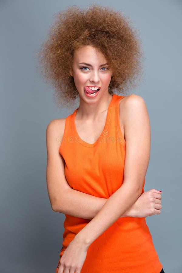 Krullend verleidelijk flirty meisje die tong tonen royalty-vrije stock afbeelding