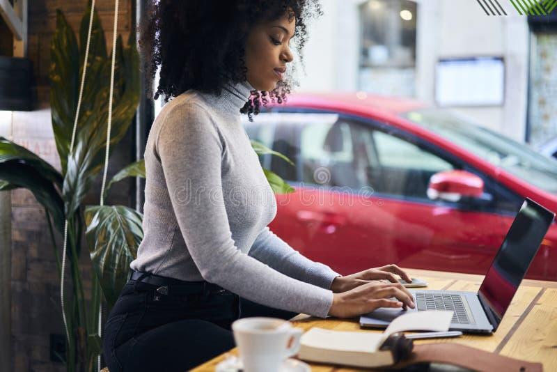 Krullende Afrikaans-Amerikaan in een grijs jasje die draadloze verbinding gebruiken aan 4G Internet stock fotografie