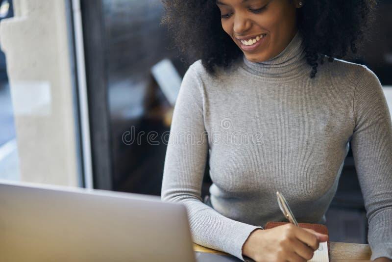 Krullende Afrikaans-Amerikaan in een grijs jasje en draadloze verbinding aan 4G Internet in de streek van koffiewifi royalty-vrije stock fotografie