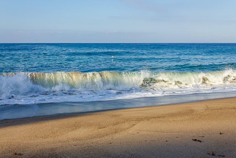 Krullende brekende golfbuis, die met terugslag op zandige kust schuimen royalty-vrije stock afbeeldingen