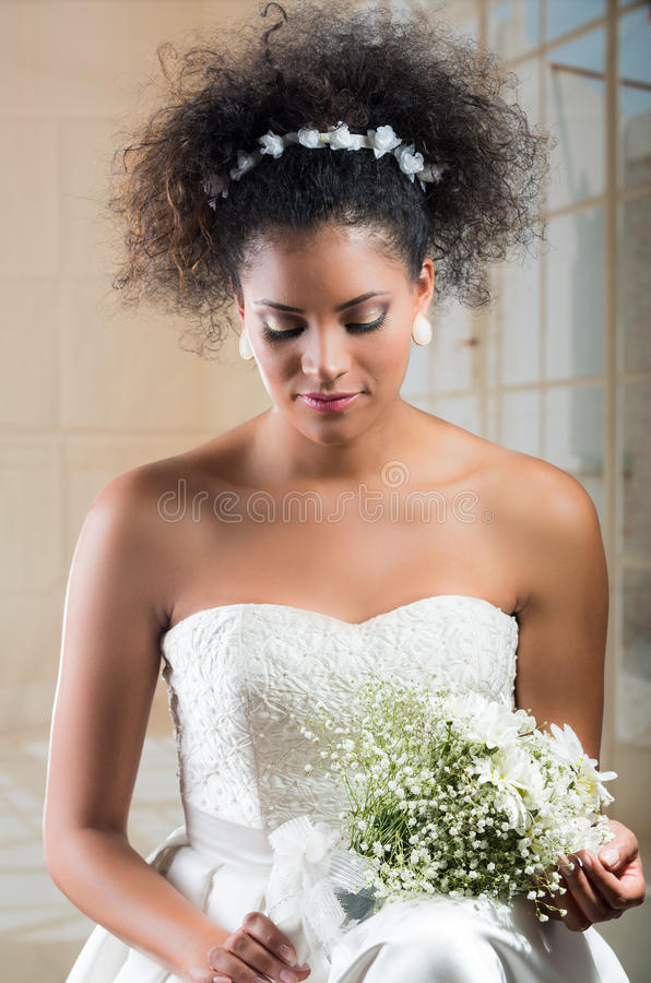 Krullende donkerbruine bruid die bloemboeket bekijken royalty-vrije stock foto's