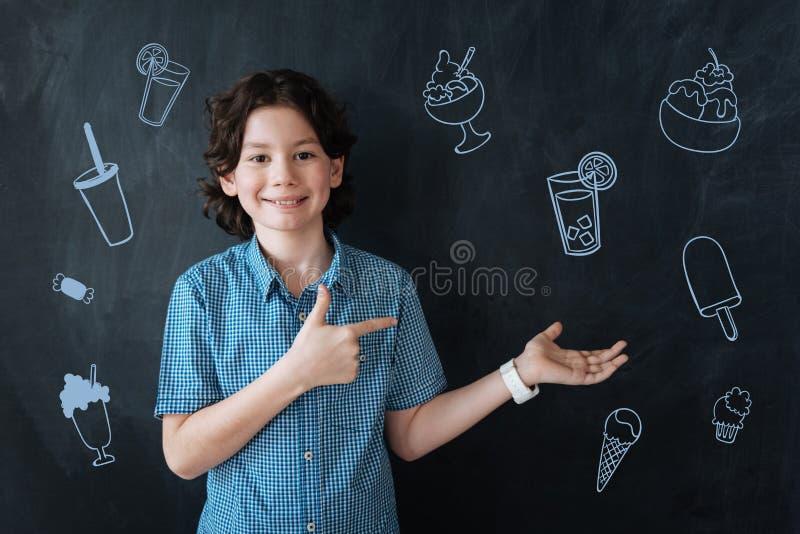 Krullende jongen die en koud dranken en roomijs glimlachen aanbieden royalty-vrije stock afbeeldingen