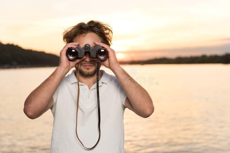 Krullende kerel met verrekijkers die iets zoeken tijdens zonsondergang royalty-vrije stock afbeeldingen