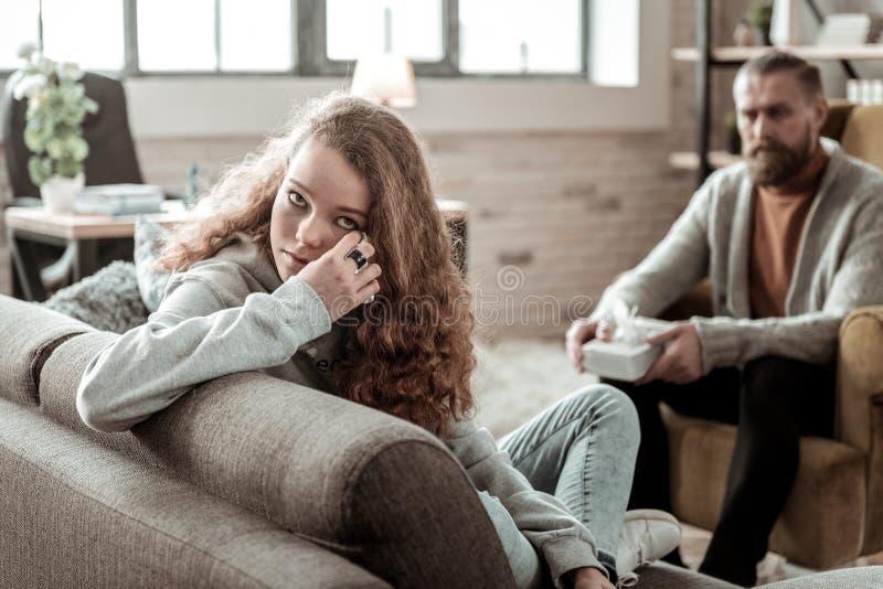 Krullende tiener die haar scheuren drogen tijdens psychologische therapie stock foto's