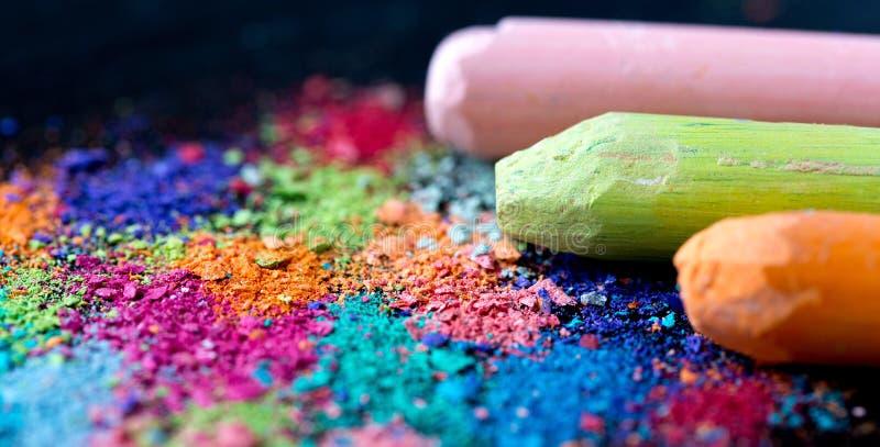Krumen der mehrfarbigen Kreide auf einem schwarzen Hintergrund Freude, Karneval, Panorama Ein Spiel für Kinder Kunst stockfoto